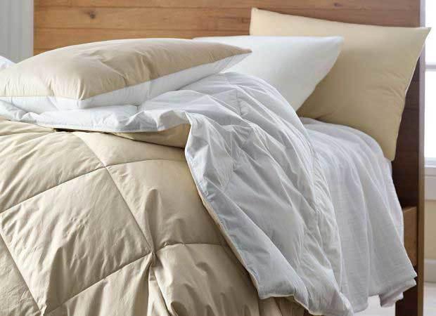 لحاف سفید پهن شده روی تخت